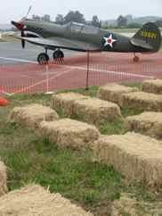 Curtiss P-40 Warhaw and spectator haybales Watsonville Fly-In